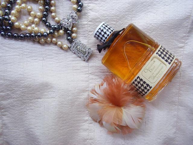 Gyöngysor és karék: szürke- beige árnyalatú gyöngyház bevonatú üveg, azaz tekla gyöngysor, strasszokkal díszes ékszercsattal, 1940-es évek Párizs, Diorissimo parfüm: teli üveg,1960-as évek Párizs,tűzhető textilvirág: toll-selyem az 1960-as évekből.