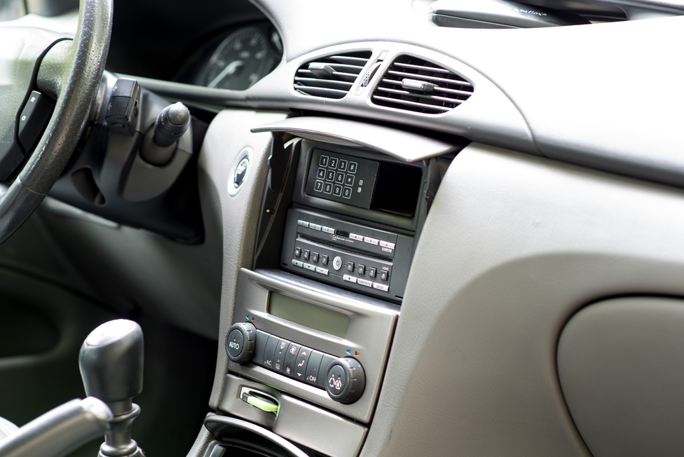 A beltéri formatervezés mindig jól ment a Renault-nál. A fejegységet eldughatjuk egy lehajtható fedél mögött, akárcsak a Honda S2000-nél. A megoldás szépsége, hogy a fedélen ismétlődik a fényszórók közötti szálcsiszolt alu-hatású betét. A felegység felett pedig a legendás Skyguard, az ezredforduló idején népszerű kódpötyögős lopás- és rablásgátló.