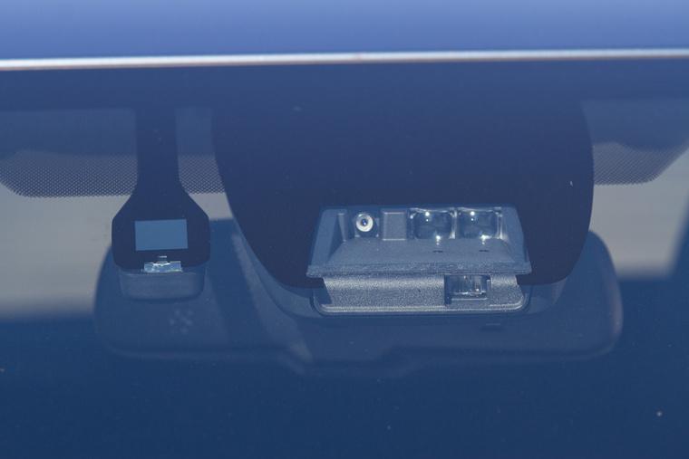 Mi ez a sok bigyó? Balra külön az esőérzékelő. A jobb oldali blokkban: Balra egy mono kamera, ez az alakfelismerő, ez látja a sávokat és a sebességkorlátozásokat és a környező járművek fényeit. Mellette a két érzékelő az alsó lézeremitter jeleit fogja, a bal oldali a szomszédos sávokat a jobb oldali a jármű saját sávját figyeli: ez a baleseti figyelmeztetéshez és a vészfékező rendszerhez szükséges
