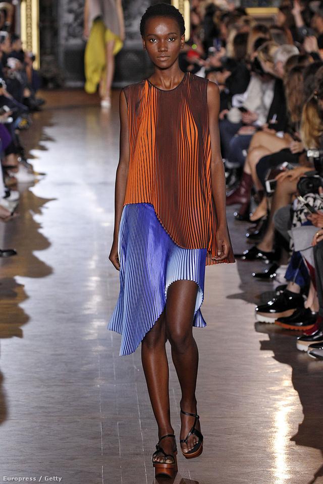 Kék rakott szoknya rozsda színű pliszírozott felsővel Stella McCartney párizsi kifutóján.