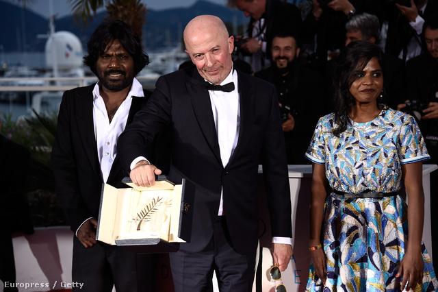Jacques Audiard rendező kezében az Arany Pálmával, és a Dheepan két szereplője, Kalieaswari Srinivasan és Jesuthasan Antonythasan