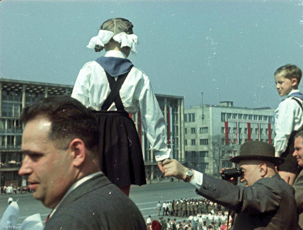 Ezen az 1955-ben készült, színes fotón Rákosi Mátyás első titkár, Hidas István, a Minisztertanács elnökhelyettese és Dobi István, A Magyar Népköztársaság                         Elnöki Tanácsának Elnöke nézi két kék nyakkendős kisdobos társaságában a május 1-i felvonulást a Sztálin téren (ma: '56-osok tere) felállított dísztribünről.