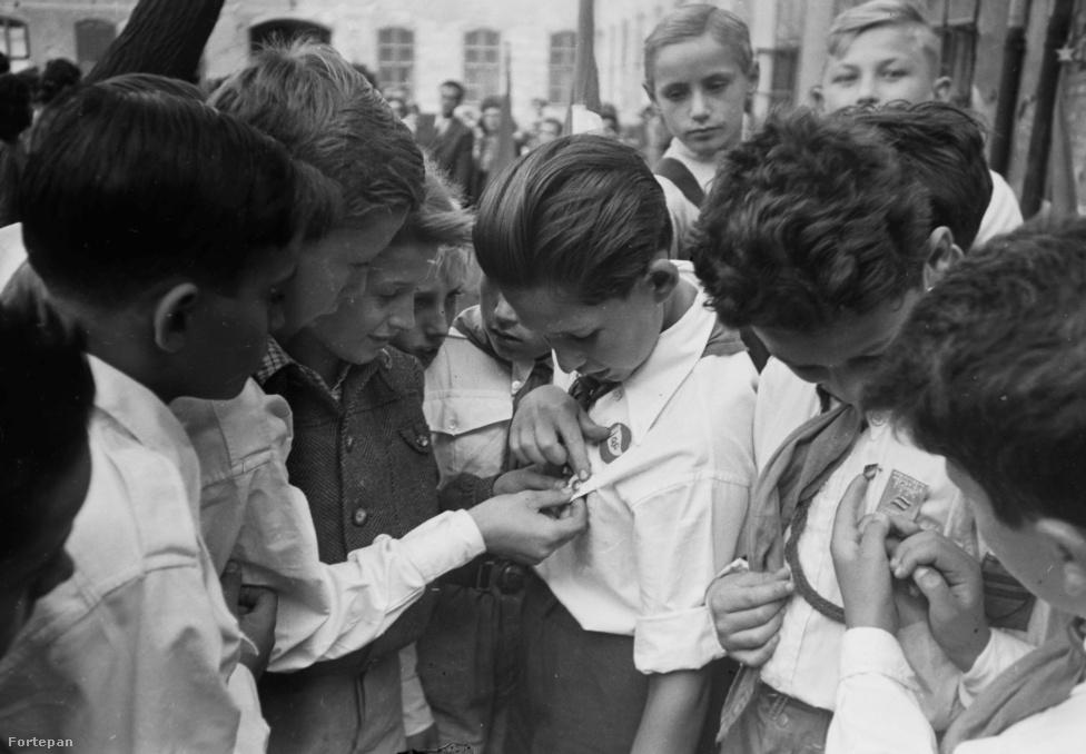 Ezen az 1949-es fotón a pajtások egymás kitűzőit és nyakkendőit nézegetik. A legelső úttörőcsapatok azonban 1945-ben még ezer féle színű nyakkendőt hordhattak, egészen az 1946-os központi szabályozásig, ami fehér színű úttörőnyakkendőt írt elő, két piros csíkkal a szélén. A fehér az úttörők jellemének a tisztaságát jelképezte, a piros csíkok pedig a forradalmiságot. A nyakkendőt ráadásul ekkoriban még nem csomózva kötötték, hanem egy piros fagyűrű tartotta össze. Az 1949-es Világifjúsági Találkozón a csapatok legjobb úttörői kitüntetésként vörös nyakkendőt kaptak – ez a viselet vált később általánossá a mozgalom teljes tagságában.
