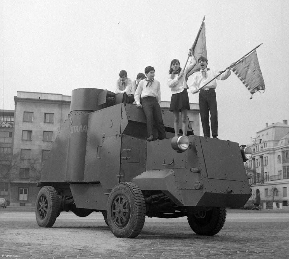 """1970-ben, amikor ez a kép is készült, fennállásának 25. évét ünnepelte a magyar úttörőmozgalom. """"Ajándék a hazának"""" címmel több ünnepséget is tartottak, valamint szolidaritási akciókkal segítették az észak-vietnamiakat és az árvízkárosult iskolákat. A fotón Lenin páncélautójának másolata látható a Felvonulási téren, amin a gyerekek az ideológiától függetlenül is örömmel pózoltak, hiszen bármilyen is a fennálló rendszer, mindig jó buli megmászni az efféle vasszörnyeket."""