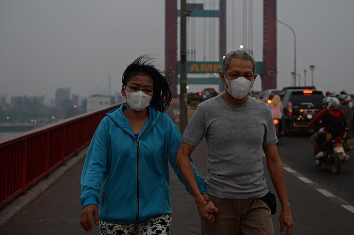 Védőmaszkos gyalogosok az Ampera hídon, Palembangban, Dél-Szumátrán, 2015. október 29-én.