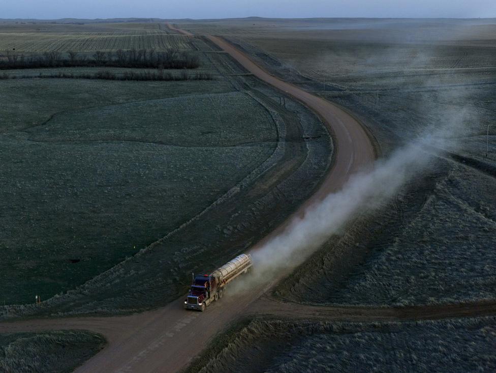 Észka-Dakotában évmilliókon keresztül csak a mínusz 40 fokos téli fagyok és a plusz negyven fokot is hozó nyári napsugarak mállasztották a hegyeket. De aztán megjelentek a nagy társaságok, melyek előbb a szénért, az olajért, majd a kétezres évekre már a palagázért túrták keresztül-kasul az állam területét. És ezzel megjelentek az új problémák, a légszennyezés, a teherautók. A kis, félreeső utak, amiket addig jóformán senki nem használt, hirtelen elképesztő méretű ipari mozgolódást kényszerültek kiszolgálni. A Dirt Meridian sorozatban Moore el akarta kerülni, hogy melodramatikus legyen. Ez nem az a hely, ezek nem azok az emberek, akiknek jól állna. De megdöbbentette a fotóst a változás, aminek a tíz év alatt a szemtanúja volt.