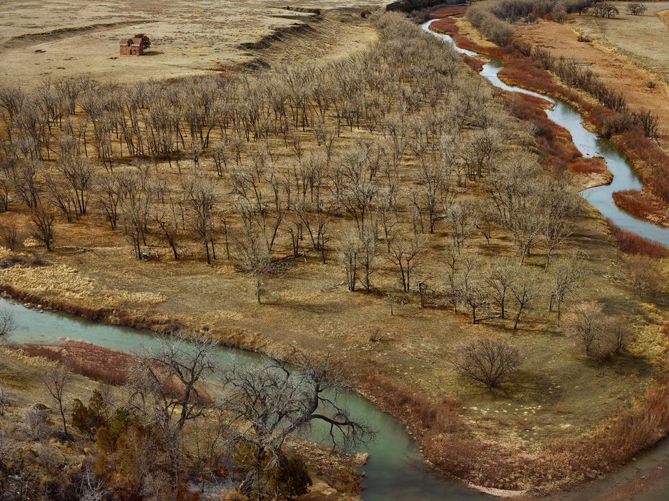 Dél-Dakotában vagyunk, az a pici kőépület 1893-ban épült a helyi vörös homokkőből. Eredileg sokkal közelebb volt a Cheyenne folyó medréhez, mint most, ezt látni a fák ívéből, ahogy idővel közelebb húzódtak a víz új útjához. A madártávlatos képeket a fotós Doug Deannek köszönheti, a permetezéssel foglalkozó pilótának, akivel összebarátkozott, és aki felvette maga mellé a kis kétszemélyes Cesna gépére. A digitális fényképezőt a fotós a szárnyhoz rögzítette.