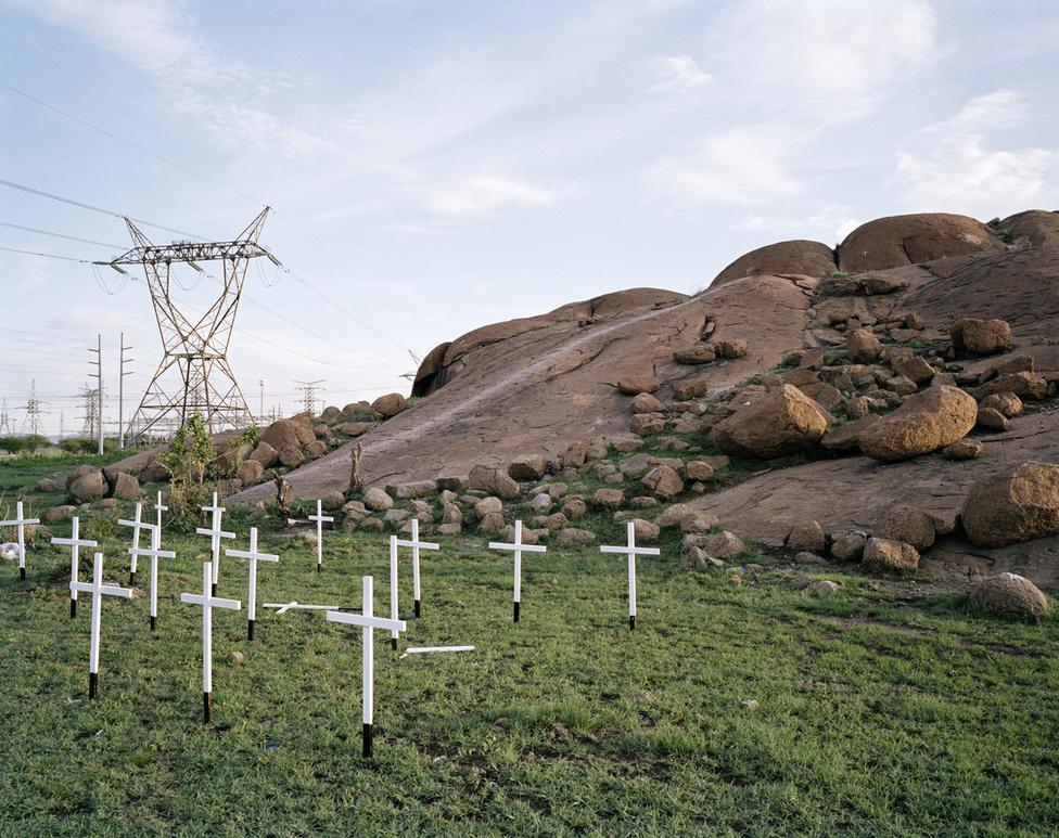 A 34 fehér fakereszt azoknak a bányászoknak állít emléket, akiket lemészárolt a dél-afrikai rendőrség 2012. augusztus 16-án. A bányászok a Lomnin nevű vállalat platinabányájánál sztrájkoltak, magasabb béreket szerettek volna. A rendőrség önvédelemre hivatkozott nyitott sortüzet rájuk. Utólag kiderült, hogy adatokat titkolt el, és hazudott a dél-afrikai rendőrség a véres eseményekről. Az áldozatokat hátulról érték a lövések.
