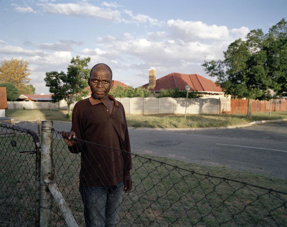 Az 50 éves Zoyisile Mgqatsa is a szilikózis egyik áldozata. 1983-ban állt bányásznak. A durva köhögés 2006-ban kezdődött. 2012-ben diagnosztizálták a gyógyíthatatlan betegséggel. Ekkor elbocsátották. A munkaadója azzal vádolta meg, hogy segít az illegális bányászoknak: aranyat rejtő törmeléket csempész ki nekik a bányából. Zoyisile Mgqatsa szerint a cég így akarta elkerülni, hogy kártérítést kelljen fizetni a betegségéért. Nem is kapott egy fillért sem azóta sem. Munkanélküli segélyből él. Becslések szerint négyből egy dél-afrikai aranybányász szilikózisban szenved. Kevesen éreznek irántuk szánalmat. A fotós, Ilan Godfrey szerint amikor nem sikerül elfedni a bányaipar sötét oldalát, a társadalom arra van kondicionálva, hogy elkezdje az áldozatokat hibáztatni.