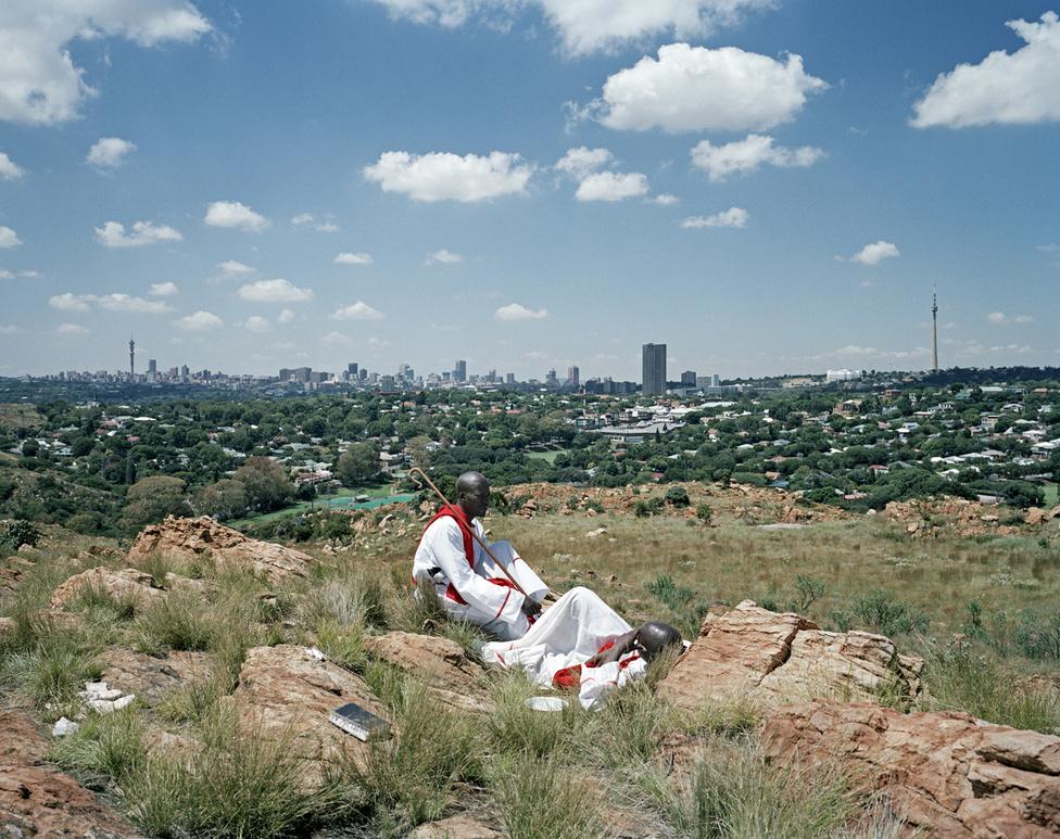 Felix Ngwenya és Nkosana Ncube a Melville Koppies nemzeti parkban pihen. Innen belátni a Witwatersrand-medencét, ahol a világ legnagyobb aranykészlete fekszik. Mindketten a zimbabwei 12 apostol egyházának tagjai: böjtölnek és imádkoznak napkeltétől napnyugtáig. Ez a hely sokak szemében szentnek számít. Ilyen volt az egész környék, mielőtt felfedezték volna az aranyat.