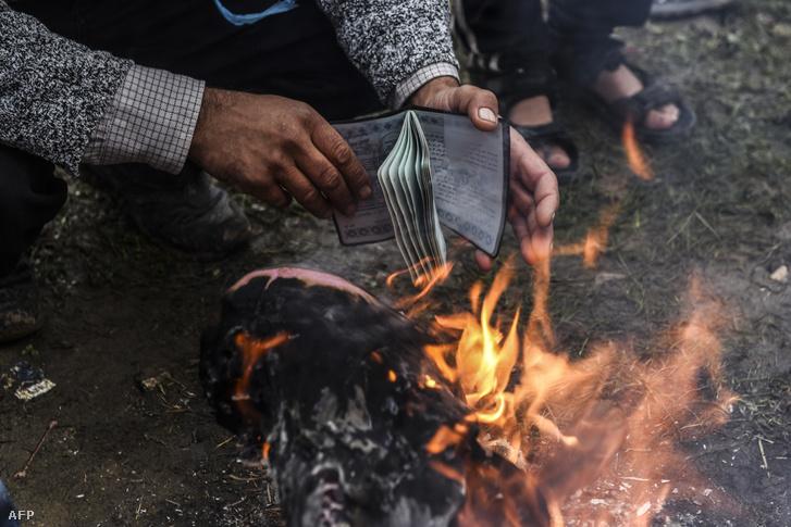 A papírjait szárítja egy menekült a tűz mellett Görögországban