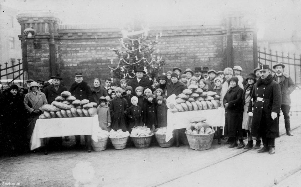 Annyit tudunk erről a képről, hogy 1920-ban készült. Módosabb emberek lehetnek rajta, mivel mindenkinek jó állapotú a ruházata, némelyek kifejezetten elegánsak. Mégis, a karácsonyi nagy dínomdánomnál azt mutatják be, hogy most nagyjából jut egy vekni kenyér mindenkinek.