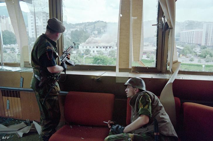 Boszniai lövészek egy szarajevói toronyház kilőtt ablaka mögött.