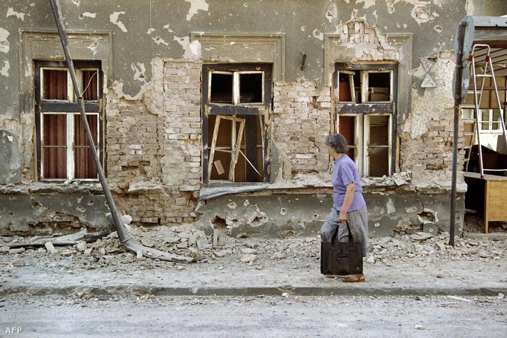 Járókelő egy szarajevói lakóház előtt, a francia kórház épületénél.