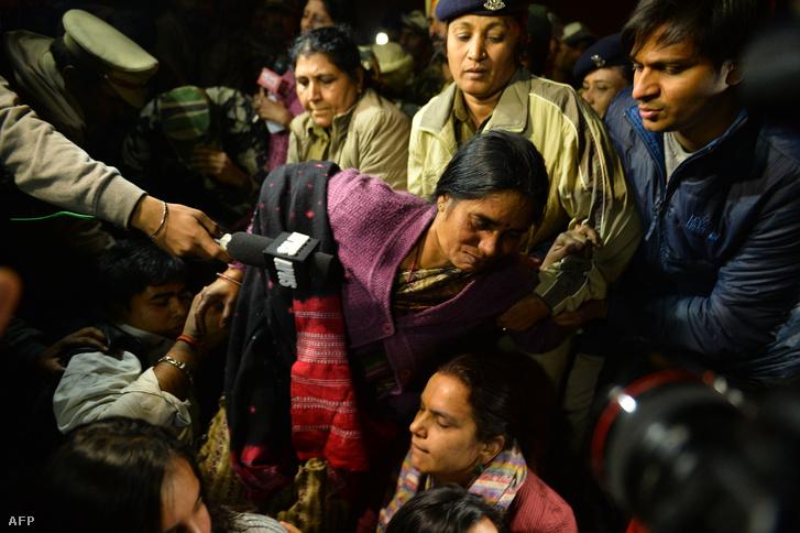 Tüntetők védik a 2012-ben meghalt lány édesanyját, akit rendőrök próbálnak elvinni az erőszak miatt elítélt fiú szabadon engedése ellen szervezett demonstráción, Új-Delhiben, december 20-án.