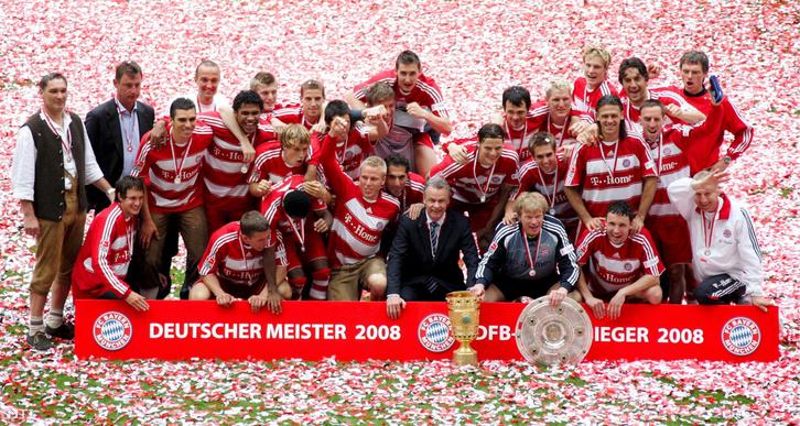 A német labdarúgó-bajnokság győzelmi trófeáját a pajzsot tartó Oliver KAHN-nal a bajnokságban győztes FC Bayern München labdarúgó-csapat visszavonuló kapusával (j-3) és leköszönő edzőjükkel Ottmar Hitzfeld-del (j-4) együtt ünnepelnek a csapattagok a Bundesligában a Hertha BSC Berlin ellen vívott búcsúmérkőzésük után Münchenben 2008. május 17-én.