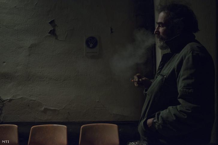 Hajléktalan férfi dohányzik a Magyar Máltai Szeretetszolgálat Rimaszombati úti krízisszállója előtt 2014. december 30-án este.