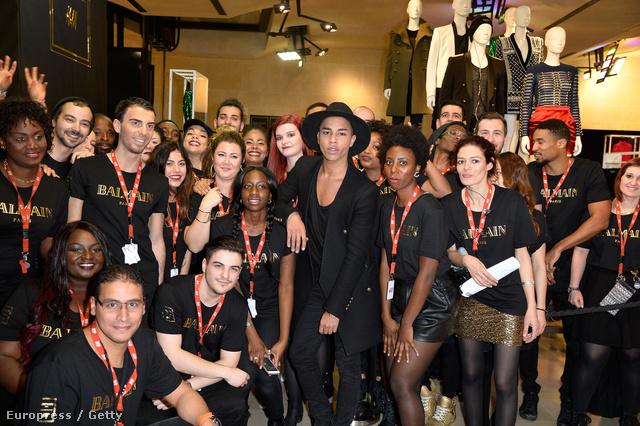 A Balmain tervezője,Olivier Rousteing pózol a                          Champs Elysees-n található H&M eladóival.