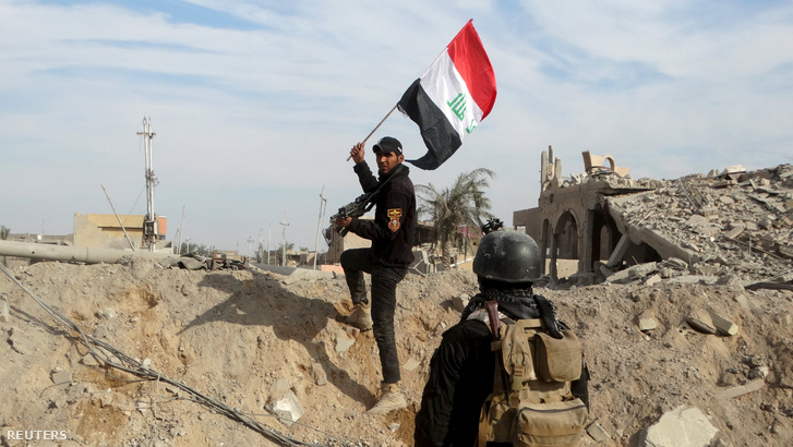 A kormányerők egyik tagja iraki zászlót tűz ki Rámadi városában, 2015. december 27-én.