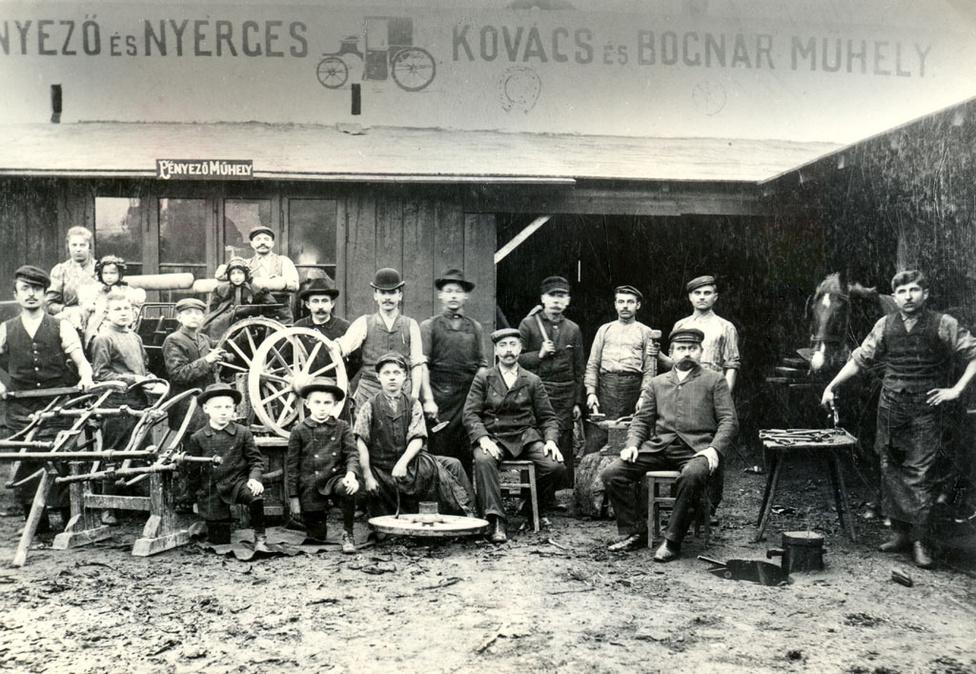 Uhry Imre kovácsműhelye 1908-ban, a jobb oldalon ülő bajuszos úriember maga a mester