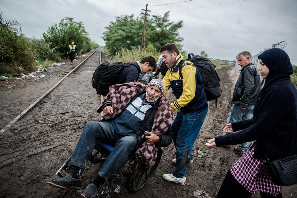 Szír menekült férfit tol be családja Magyarországra, mielőtt még lezárták volna a határt Röszkénél. Minden egyes nap borzalmasabb dolgot lehetett látni a kerítésnél, mint előtte. Hosszú kilométereket gyalogló elcsigázott emberek. Hosszú kilométereken keresztül cipelt pólyás gyerekek. Hosszú kilométereken át esőben cipelt pólyás gyerekek. Nekem mégis ez a kép maradt meg. Egy félkész kerítés. A sár. A mindent ellepő fáradtság, ahol minden borzalom természetes, az élet magától értetődő velejárója.