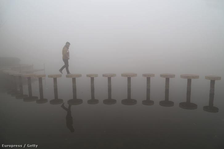 Hídon sétál egy kínai kiránduló a szmogban
