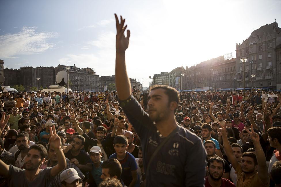 """Menekültek rögtönzött tüntetése a lezárt Keleti pályaudvar előtti téren. A napok óta várakozó emberek száma kétezerre duzzadt a pályaudvar alatti aluljáróban, odafenn pedig több száz fős tüntetés szerveződött. ahol a pályaudvar megnyitását követelték. """"Szabadság, Szabadság"""" - kiabálták angolul. Másnap reggel megnyitották az állomást, és elindult a menekültek utaztatása Ausztrián keresztül Németország felé."""