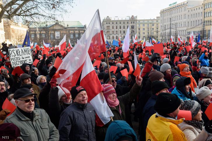 Demokráciát követelő kormányellenes tüntetők piros lappal a kezükben tiltakoznak a novemberi lengyel parlamenti választásokon győztes Jog és Igazságosság (PiS) párt ellen Poznanban 2016. január 2-án.