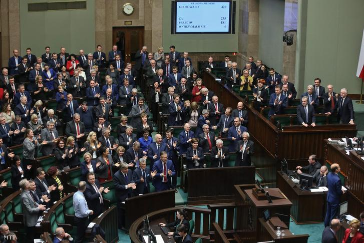 A kormányzó a Jog és Igazságosság (PiS) párt képviselői tapsolnak miután a lengyel parlament alsóháza a szejm megszavazta az alkotmánybíróságról szóló törvény módosítását