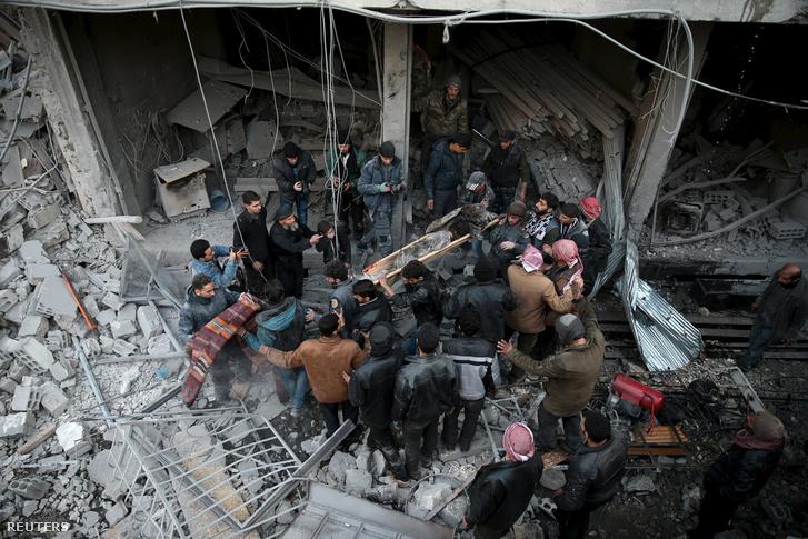 Holttestet emelnek ki a romok közül egy orosz légicsapás után január 10-én, Douma belvárosában.