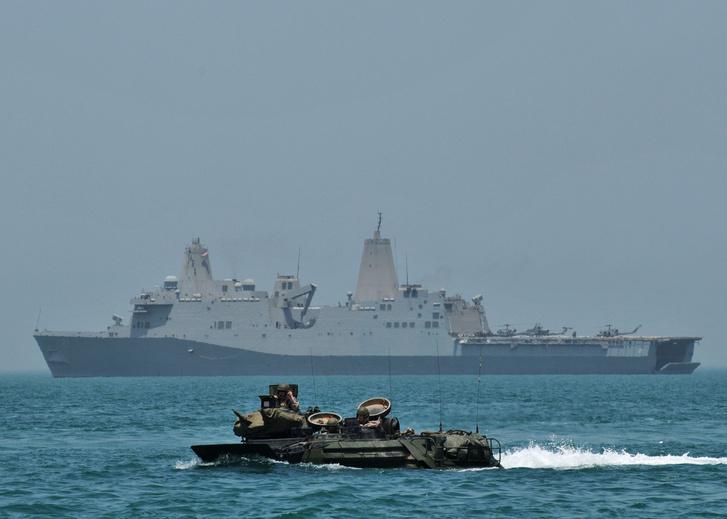 Egy kétéltű jármű szeli a habokat az Arab-tengeren, háttérben a USS New York partraszálló hajó.