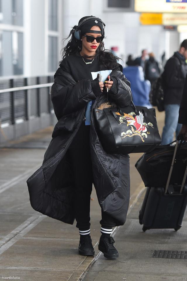Rihanna játszósnadrággal, hátra fordított sapkával és összefestett dizájner táskával viselte a paplankabátot a New York-i JFK reptéren.