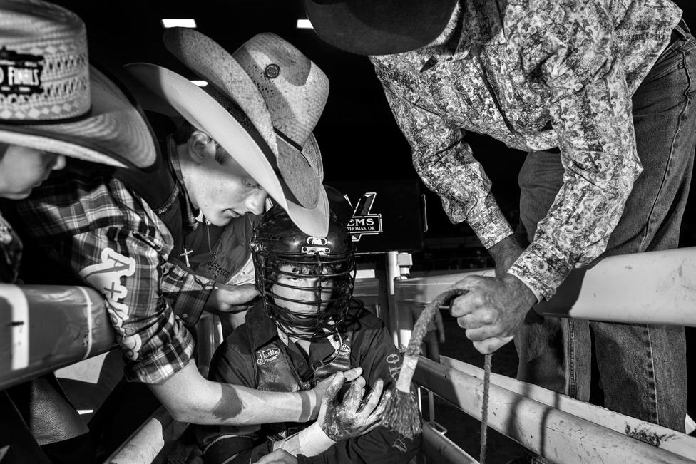 Ez egy olyan sport, ahol a páros egyik tagja megpróbálja megölni a másikat. Mintha jégtáncolni kellene egy baltás gyilkossal: körülbelül ilyen a bikarodeó az amerikai újságíró, Burkhard Bilge szerint, aki a New York-i fotóssal, Jonno Rattmannal a texasi Abilene-ben versenyző gyerekcowboyokról készített anyagot a New Yorker számára 2014-ben. Ezek itt a képen egy Blake Solmi nevű kisfiú utolsó pillanatai azelőtt, hogy elkezdődött volna a harmadik menete a világbajnokság döntőjében. Végül nem sikerült pontot szereznie ebben a körben.