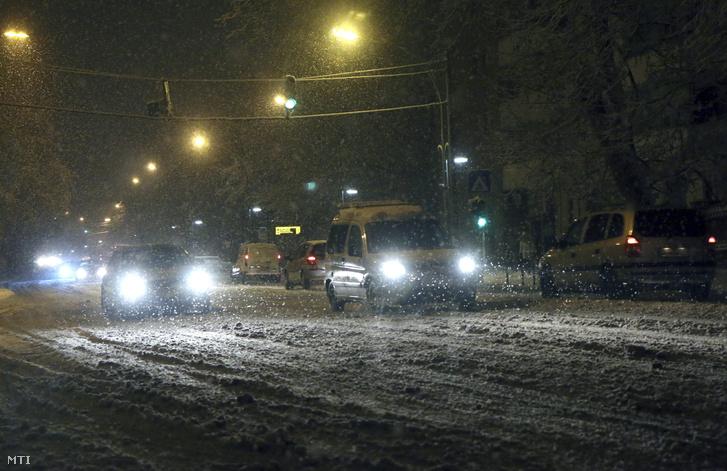 Autók haladnak a sűrű hóesésben Miskolc belvárosában a Görgey Artúr utcában 2016. január 15-én reggel.