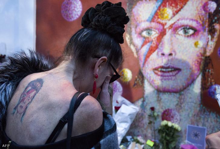 Egy rajongó helyez el virágot Brixtonban