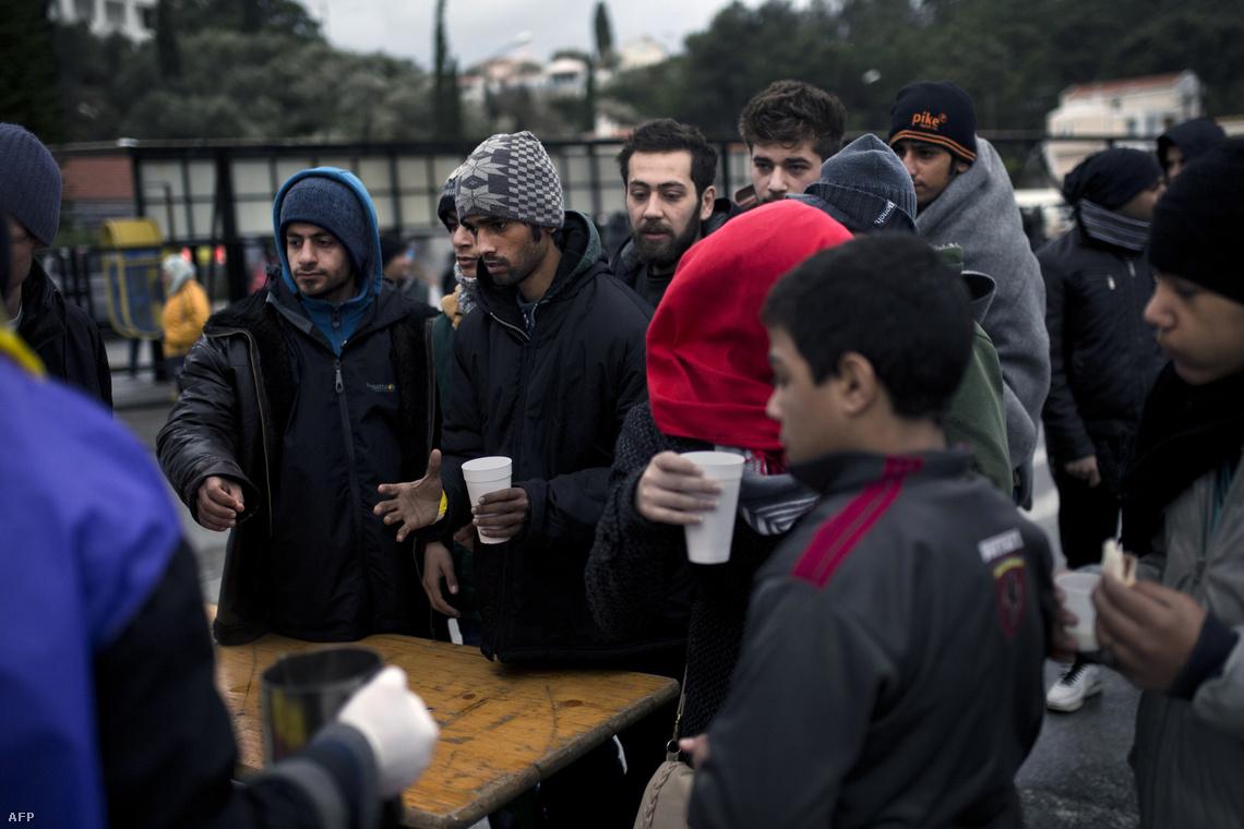 Menekültek melegednek egy pohár tea mellett a regisztrációs ponton a görög Szamosz-szigeten