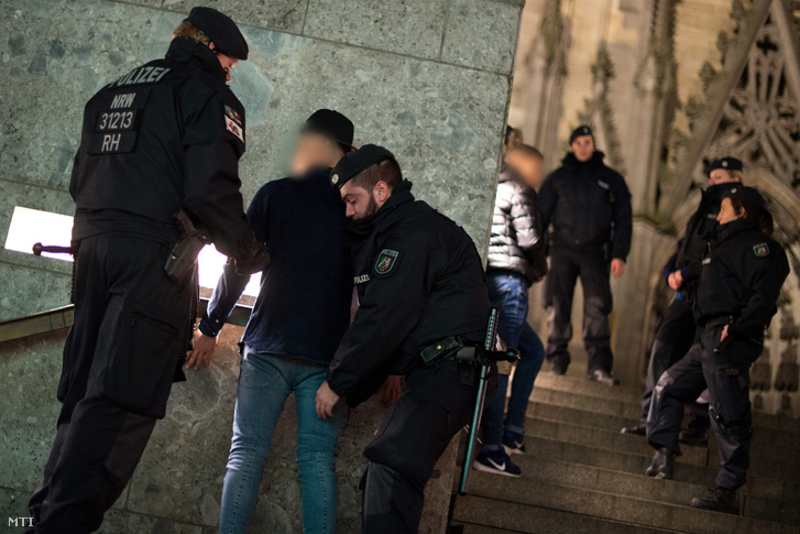 Rendőrök igazoltatnak gyanúsítottakat a kölni főpályaudvarnál 2016. január 6-án.