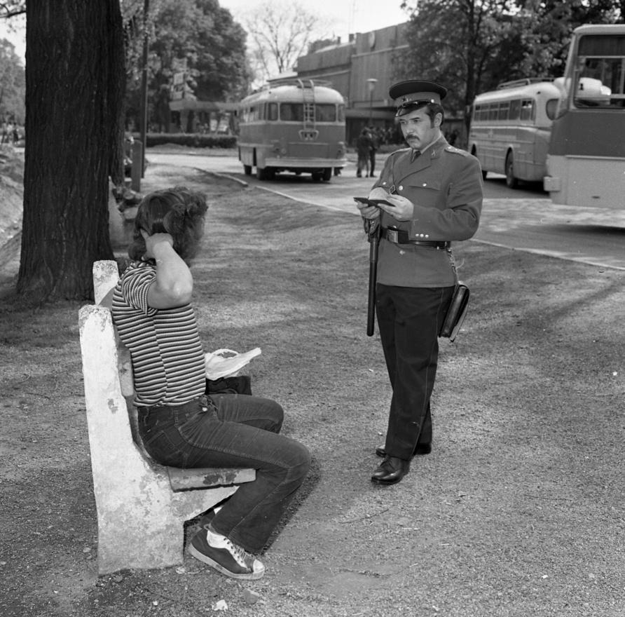 Üldögélünk, üldögélünk? Gyanús lumpen elemet igazoltat a szemfüles rendőr, az pedig álnaivan vakargatja lázadó frizuráját. Még egy remek helyszínelőfotó.