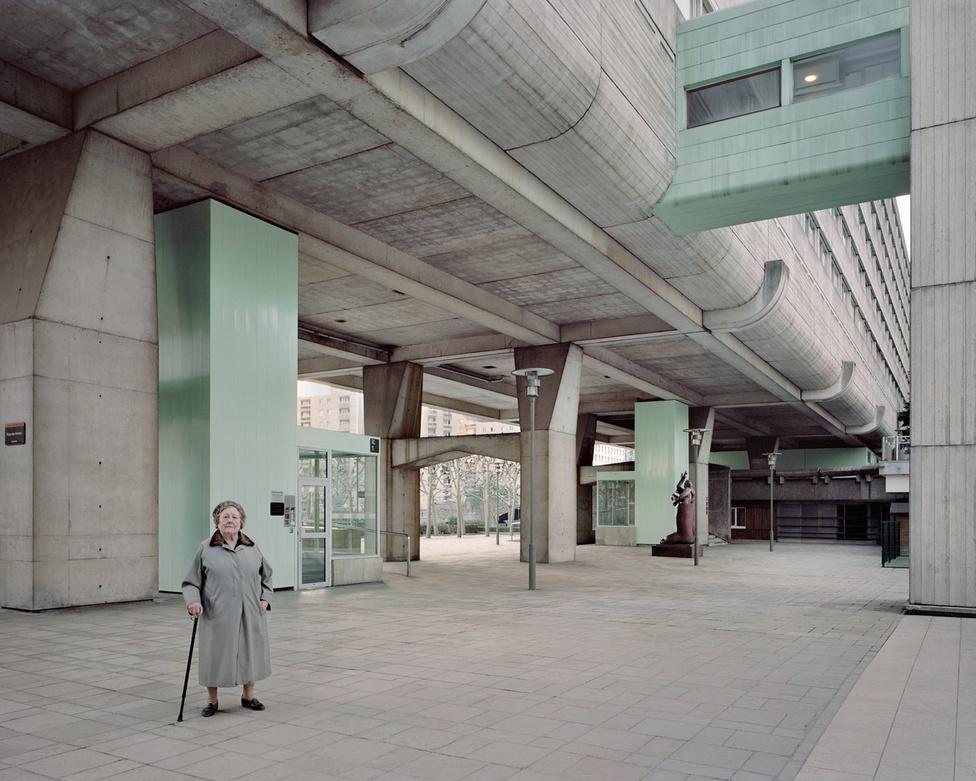A La Défense Párizs egyik fontos, a történelmi városmagtól nyugatra elterülő üzleti központja, ahol minden csupa beton, üveg és acél. A képen látható, oszloplábakon álló emeletes ház megálmodója Jean-Pierre Jouve, Andreï Frieschlander és Charles Mamfredos voltak, 1973-ban. A geometriai síkok és szögek letisztult rendszerét csak egy 90 éves helybéli asszony, Josette alakja töri meg, aki szerencsére lifttel fel tud jutni a felsőbb szintekre. A fotó 2013-ban készült.