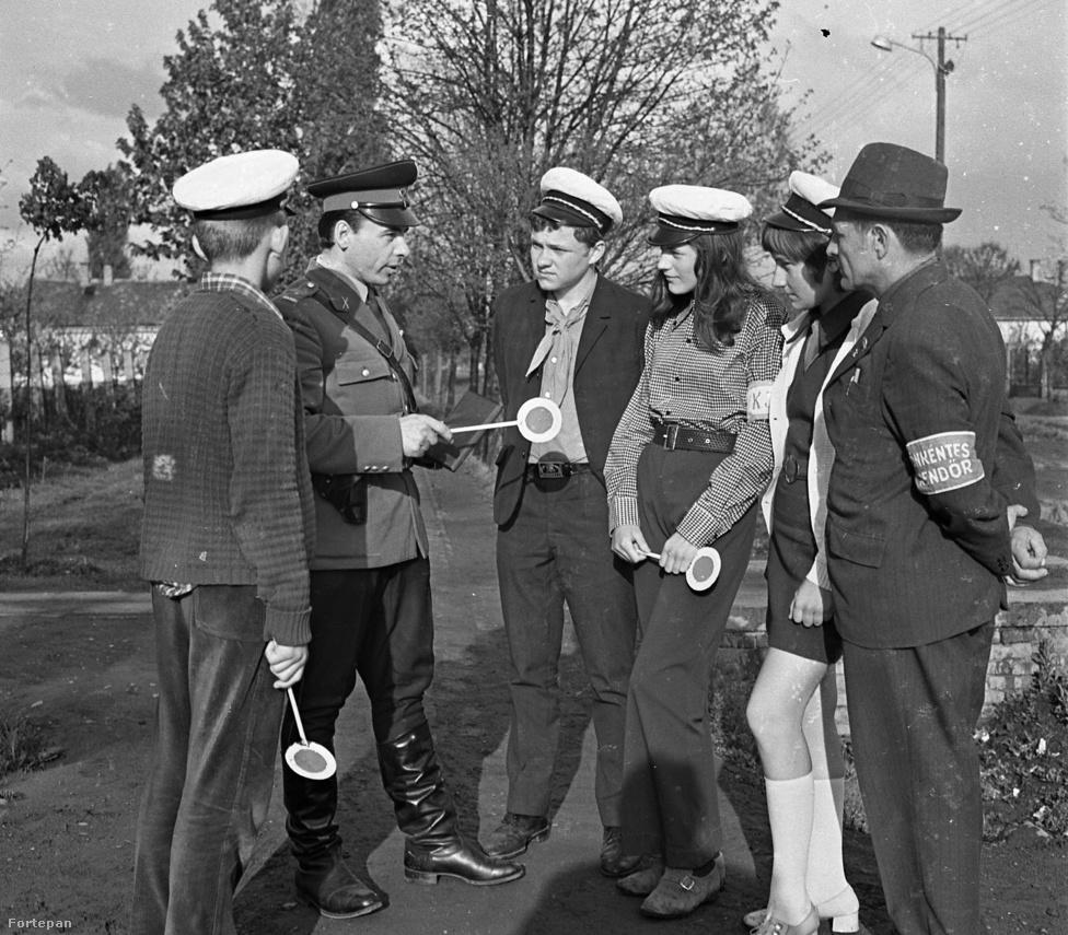 """Az év 1972, és épp csinos forgalomirányítókat oktat egy rendőr egy önkéntes rendőrrel. """"Az önkéntes rendőr ahol tud, segít, ahol nem akarják, ott is"""" - ez volt a mondás. Az önkéntesek """"állampolgári kötelességük tudatában, aktívan kívántak bekapcsolódni a társadalmi tulajdon, a közbiztonság és a közrend védelméért folytatott harcba, hogy mint önkéntes rendőrök fejtsék ki tevékenységüket""""."""