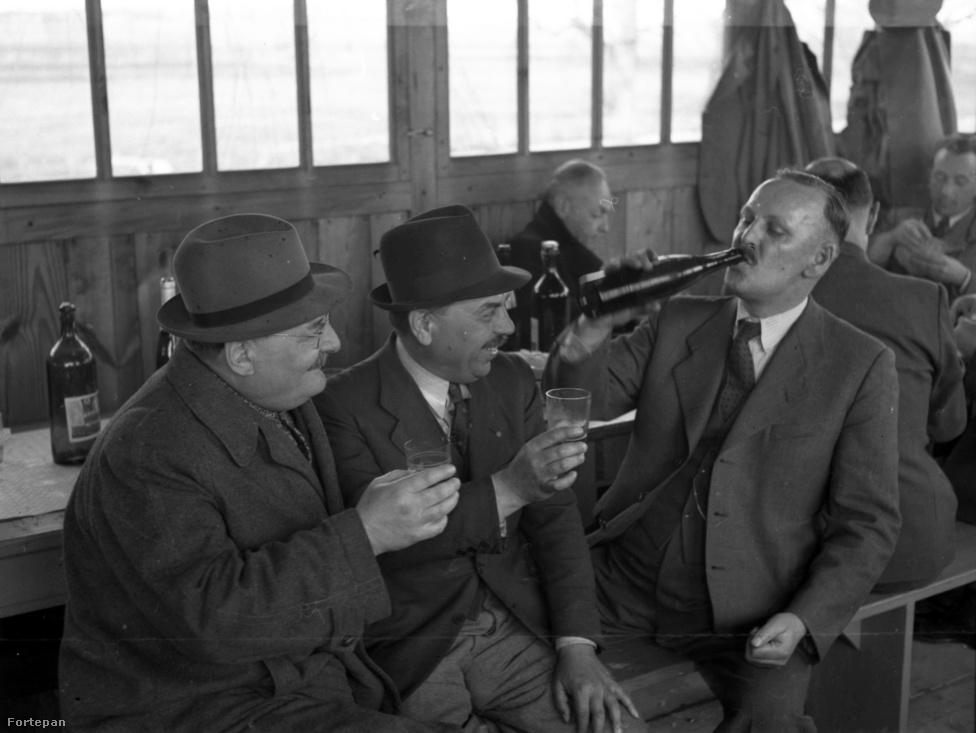 """Söröző társaság a kőbányai """"Mi csárdánkban"""" 1942-ben. Ebben az évben leváltották a Bárdossy-kormányt és helyette Kállay Miklós kabinettje vette át. A németek még folyamatosan szorították vissza a szovjet csapatokat, és úgy festett, biztos lesz a győzelem. Az anyaországban viszont a jobb alapanyagokat a had- és gyógyszeripar kapta. Most a kézműves sörfőzdék tarolnak, ha olyan nyersanyagokból dolgoznak, mint a muhar vagy a cikória, a '40-es években viszont kifejezetten rossz sörök készültek ezekből és lóbabból vagy cirokból."""