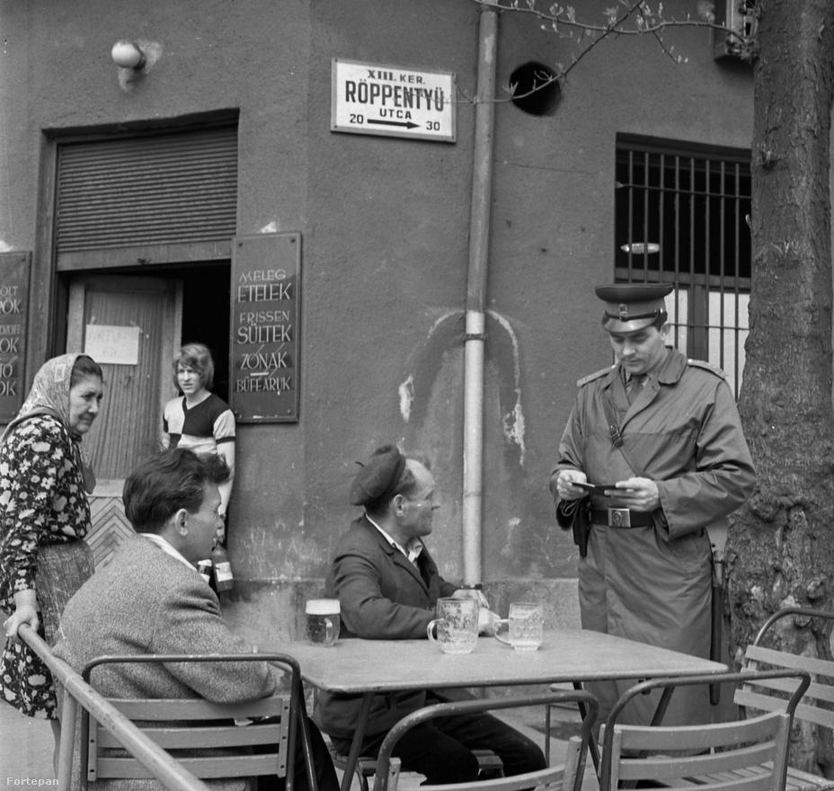 Rendőr igazoltatja a kocsmában italozó társaságot a Röppentyű utcában 1972-ben. 1949 és 1989 szigorúan tilos volt az utcán alkoholt fogyasztani, a kivételt csak a kocsmák kerthelyiségei jelentettek. A rendőrök azonban nem vették szigorúan a törvényt csak délelőtt. Aki akkor az utcán ivott, jó eséllyel krónikus munkakerülő volt.