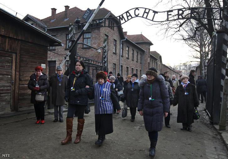 Túlélők az egykori auschwitz-birkenaui náci koncentrációs tábor főkapuja fölötti hírhedt az Arbeit macht frei (a munka felszabadít) felirat alatt a lengyelországi Oswiecimben.