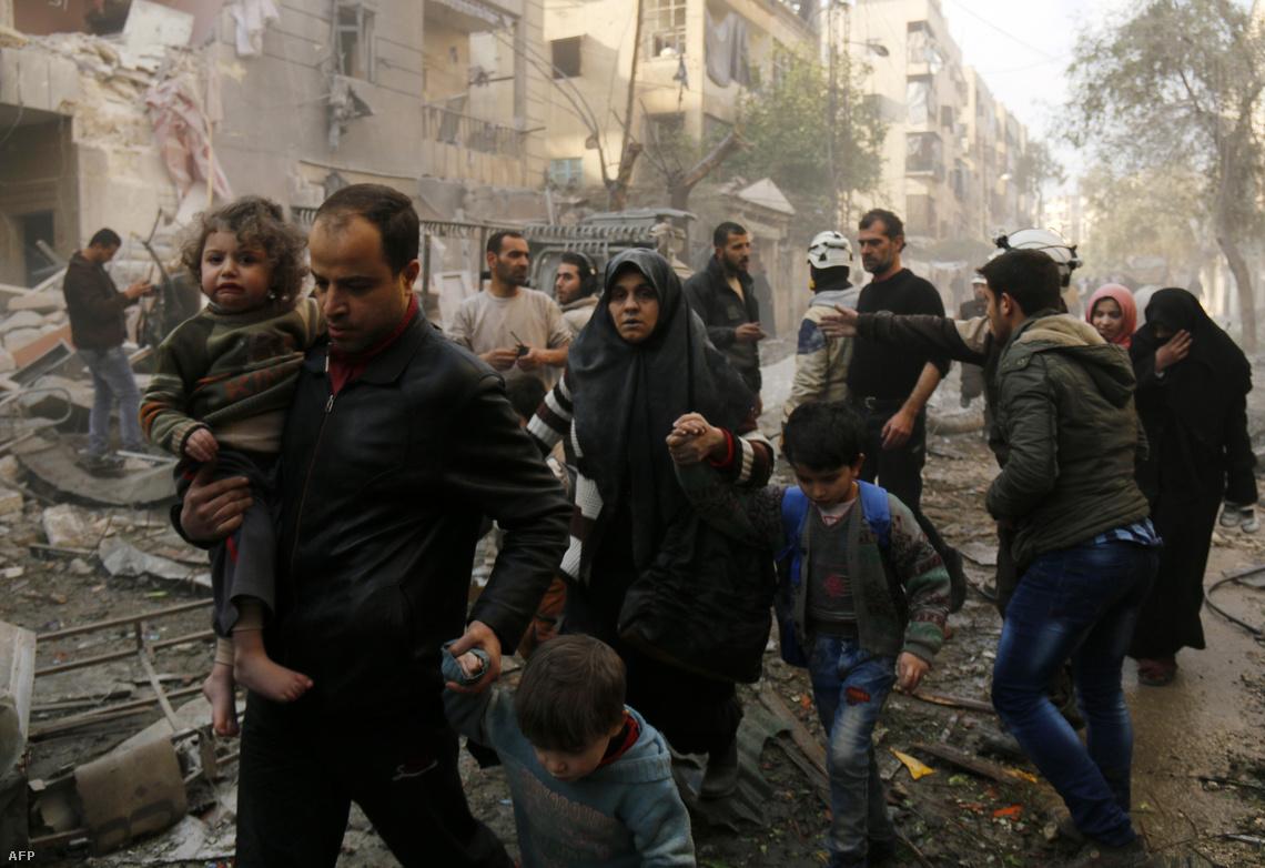 Egy aleppói család a lebombázott otthonuk romjai előtt