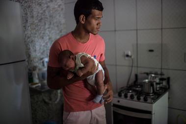Matheus Lima a két hónapos fiával házuk konyhájában. A gyerek mikrokefáliával született decemberben.