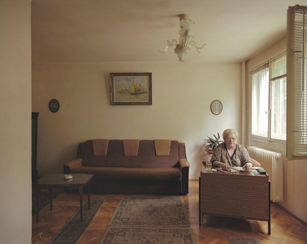 """""""Az osztályok nélküli társadalom"""" vízióját viszont egész jól el lehet egy ilyen ház alapján képzelni a fotós szerint: egy fedél alatt élnek orvosok, professzorok, munkások, bányászok, mérnökök, nyugdíjasok, még földművesek is. Gîrbovan házában a legalsó szint viszonylag új lakóé, a nevét titokban tartó asszonyság csak tíz éve költözött be. 1989 előtt bankjegyektervező grafikus volt a román nemzeti banknál. Az egyforma szobákba, egyforma körülmények közé kényszerítés egyfajta uniformizálási kísérlet volt. Bogdan Gîrbovan fotói alapján szerencsére messze nem sikerült tökéletesen."""