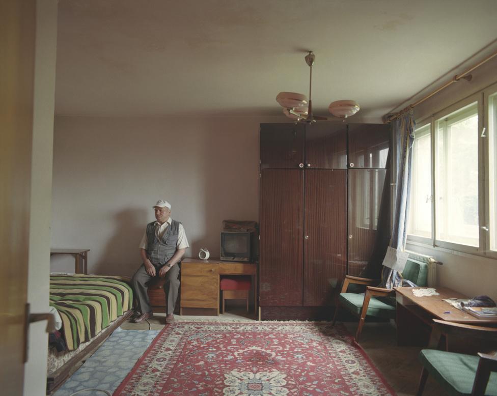 """A harmadik emeleti lakás éppen üresen állt a projekt idején, árulták a tulajdonosok, akik külföldön éltek. A házmesternek viszont volt kulcsa, ő engedte be szívességből a fotóst, és aztán azt is megengedte, hogy látszódjék a képen, egy feltétellel: """"Nem fogok belenézni a kamerába. Tudja, végülis én vagyok házmester.""""                         A ház 1966-ban. A sztálini terv lényege az volt, hogy egyforma lakóházak épüljenek olcsó lakhatást adva a gyárak miatt a városokba költöztetett parasztoknak. A lakások kicsit voltak, a családnak nem volt helye ahhoz sem, hogy együtt leüljenek enni, de közben valaha elképzelhetetlen komfortot kínáltak folyóvízzel, elektromossággal, szennyvízelvezetéssel."""