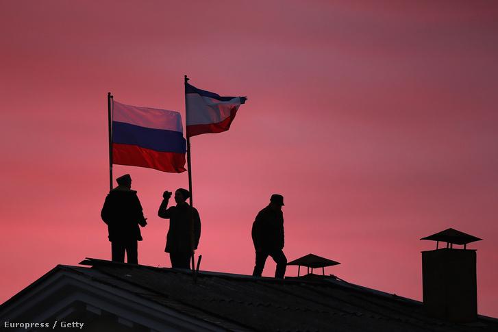 Orosz katonák helyezik ki az orosz zászlót egy krími városházra.