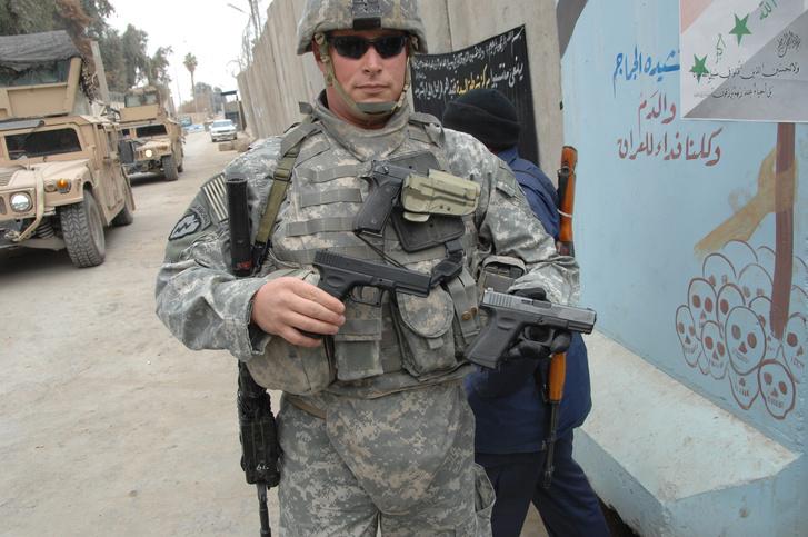 Egy valódi 9mm-es és egy játékpisztolyt tart a kezében egy amerikai katona Irakban