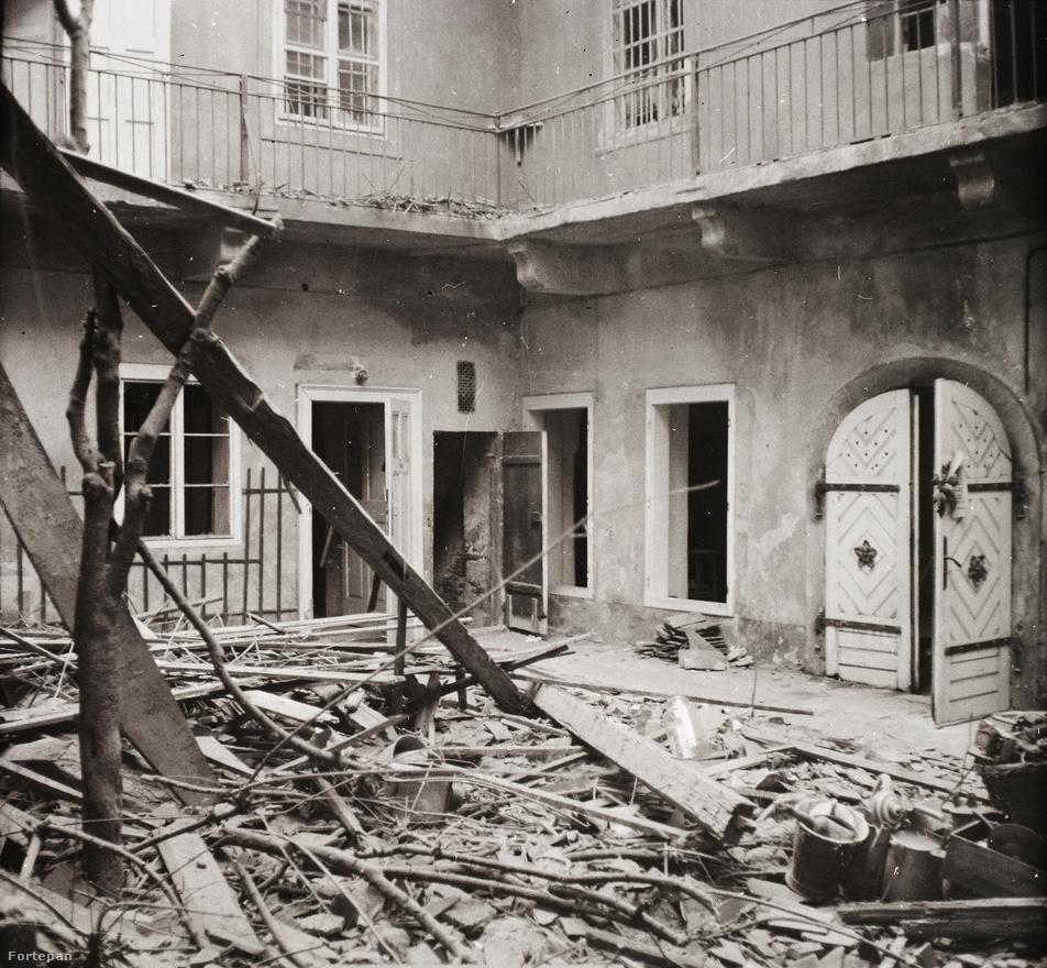 Az Úri utca 19. felső szintjéből szinte csak a főfalak álltak a két nagy bombatalálat és a sok kisebb belövés után. De az egész Várban is, összesen négy lakás maradt meg épen, a Várnegyedet teljesen szétlőtték február 13-áig. A lakók és a menhelyen elhelyezett gyerekek az óvóhelyen bújtak meg, ennek lejárata az a díszes udvari kapu, mely itt is látható. Ez a Vár alatti nagy háromszintes pincerendszerbe vezet, melynek a legalsó részét ekkor a Sziklakórház használta, de még így is viszonylag biztonságosnak számított a mély sziklapince. Ezekben nem kis zsúfoltság volt: sokan jöttek ide rokonok a város más részeiről, és szomszédok is azokból a Várban lévő házakból, ahol nem volt saját pince.